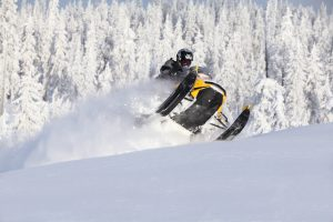 Snowmobile splashing snow with snowy pines in the background